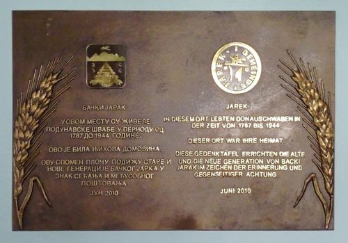 Picture 11 – The new Jarek Memorial plaque in the foyer of the town hall in Bački Jarak. Below both municipal coats-of-arms of Bački Jarak (left) and of Jarek (right) each contains the same text in the Serbian and German language.